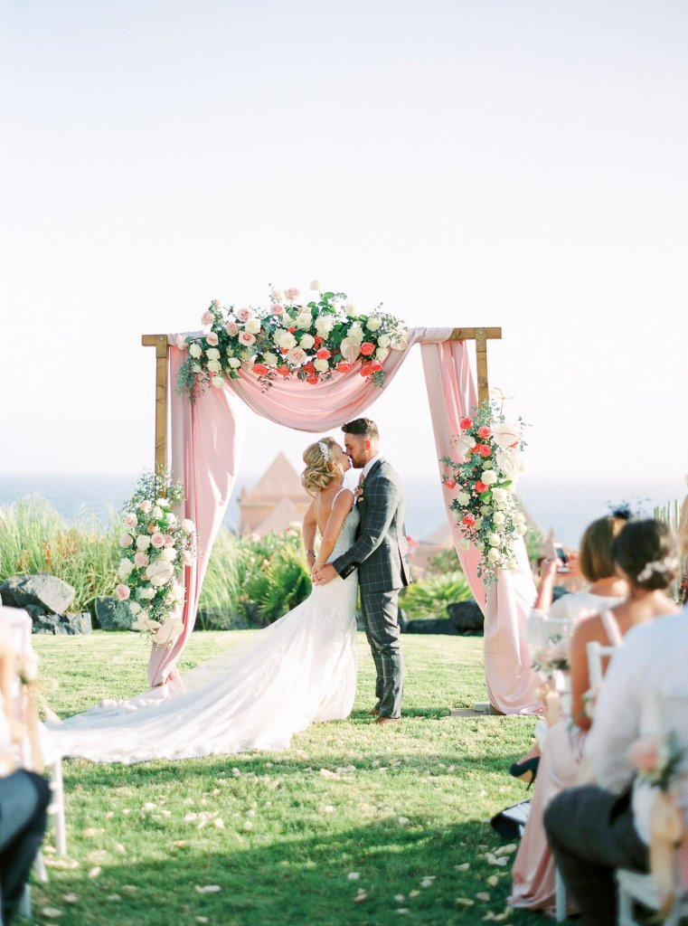 bride and groom near wedding arch